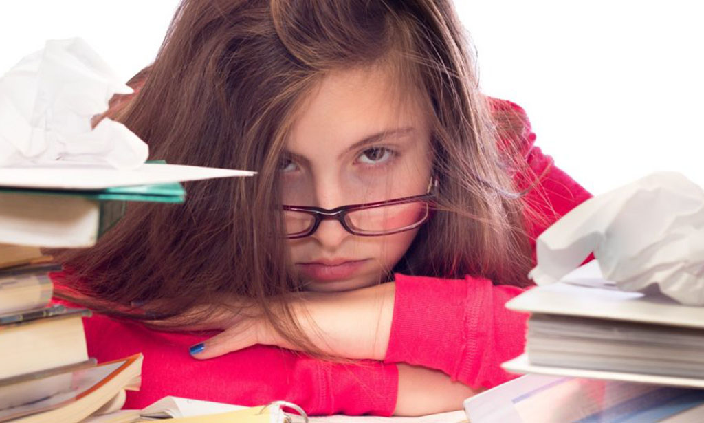 Teenage girl surrounded by School books looking frustrated