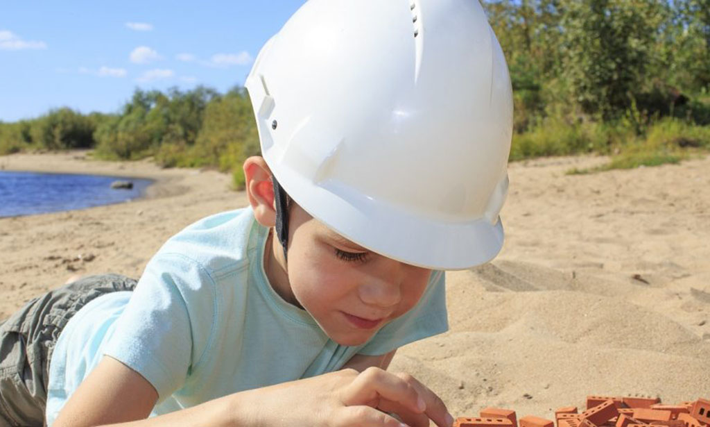 to play in construction. boy in a helmet is building a house out of bricks on the river bank