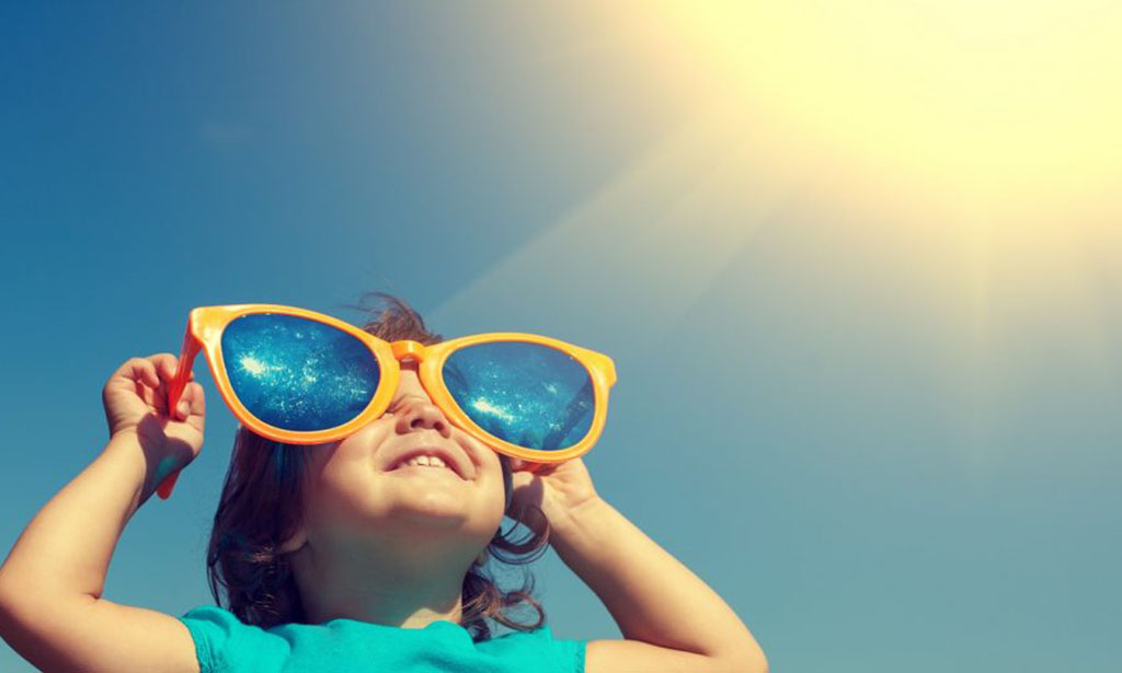 Happy little girl with big sunglasses looking at the sun